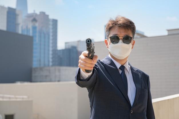 Een aziatisch mannetje met een pistool met een zonnebril en een masker in de stad.