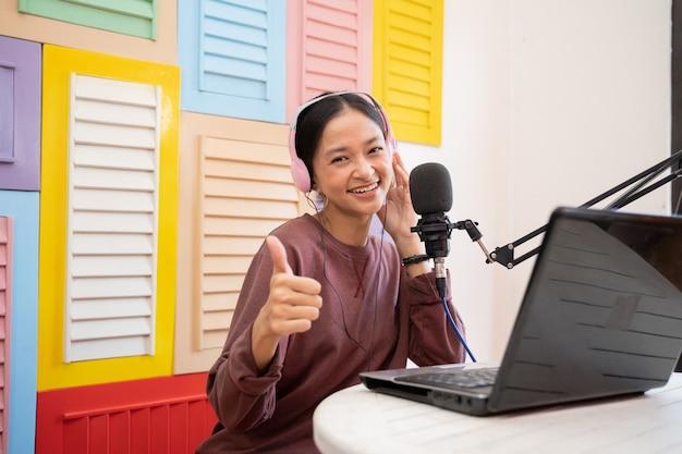 Een aziatisch meisje dat in de microfoon praat tijdens het opnemen van een videoblog met duimen omhoog