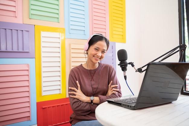 Een aziatisch meisje dat nonchalant lacht voor een microfoon terwijl ze een videoblog opneemt met gekruiste handen
