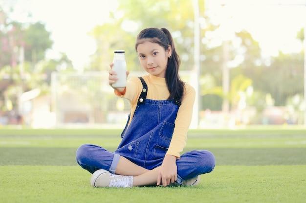 Een aziatisch meisje drinkt een heerlijke fles melk.