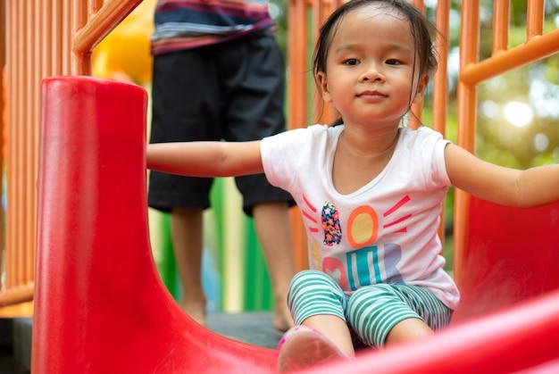 Een aziatisch meisje geniet op een speeltoestel in een school.