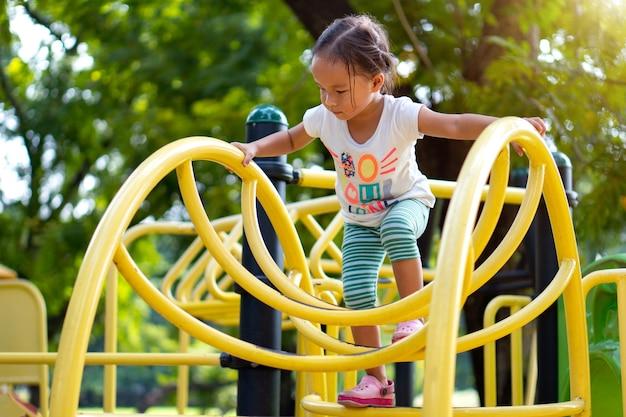 Een aziatisch meisje klimt op een speeltoestel in een school.