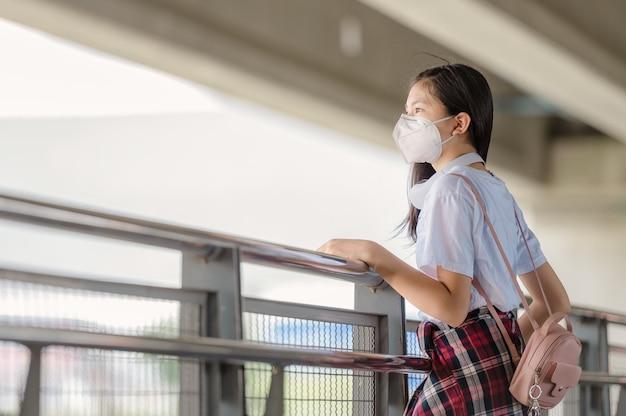 Een aziatisch meisje met een masker loopt neerslachtig op een voetgangersbrug.