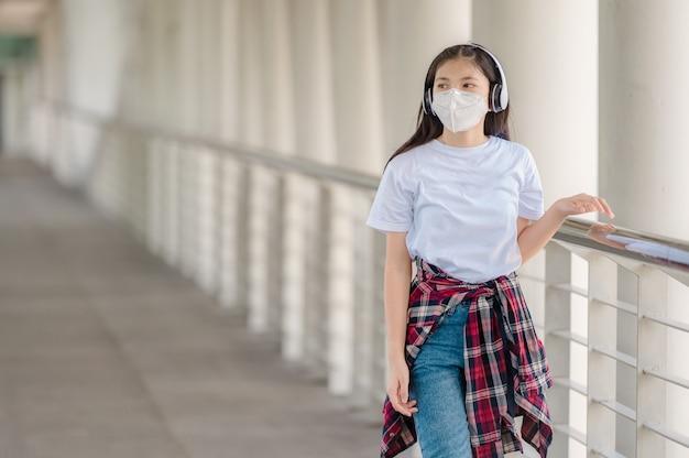 Een aziatisch meisje met een masker loopt op een voetgangersbrug.