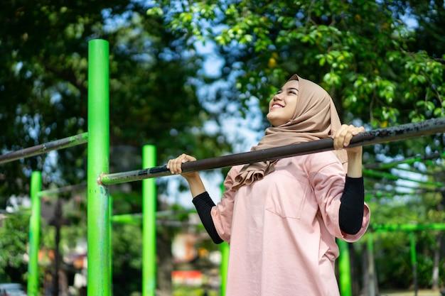 Een aziatisch meisje met een sluier trekt zich omhoog om haar handspieren in het park te trainen