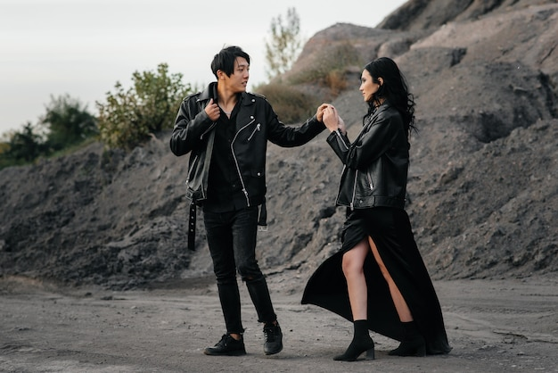 Een aziatisch paar verliefd in zwart lederen kleding lopen in de natuur tussen de bomen. stijl, mode, liefde
