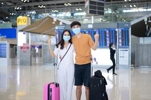 Een aziatisch stel draagt een beschermend masker op de internationale luchthaven, reist onder covid-19 pandemie,