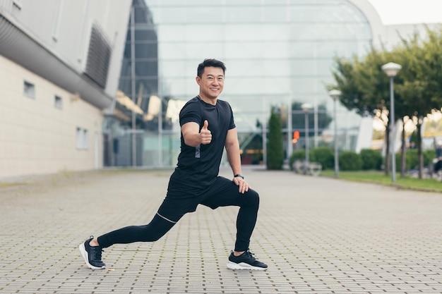 Een aziatische atleet die fitness doet, glimlacht en kijkt naar de camera die zijn uitgestrekte hand vasthoudt en zijn duim laat zien