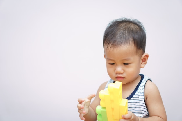 Een aziatische baby van 1 jaar en 4 maanden die plastic blokken speelt