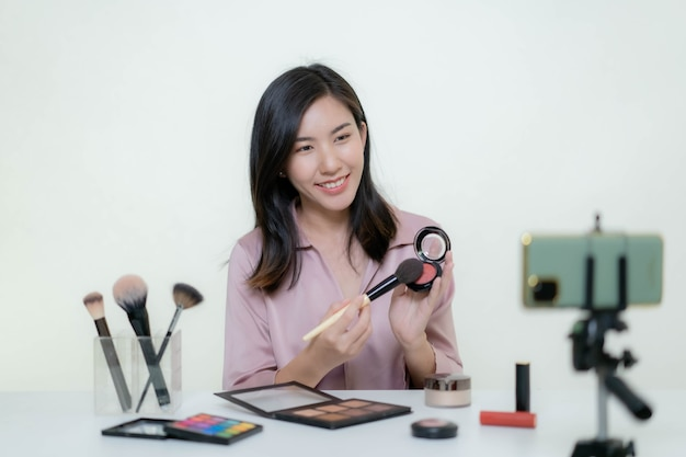 Een aziatische blogger, beautyblogger, maakt een video van zichzelf terwijl ze een oranje lippenstift draagt in een studio.