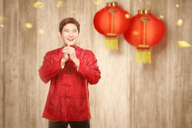 Een aziatische chinese man in een cheongsam jurk met gefeliciteerd gebaar