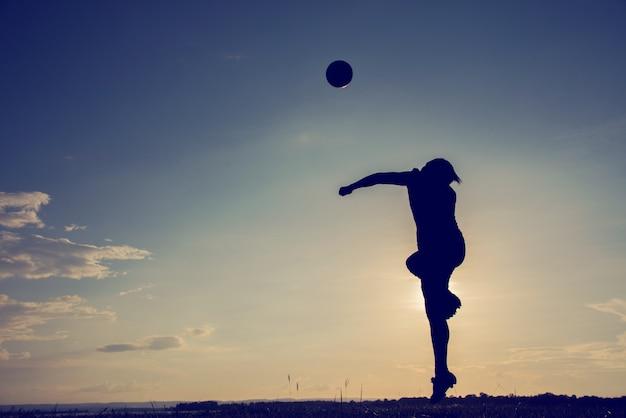 Één aziatische de jonge mensenrubriek van de voetbalvoetbalster in silhouet