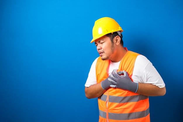 Een aziatische dikke arbeider die een veiligheidshelm draagt, voelt pijn in zijn borst