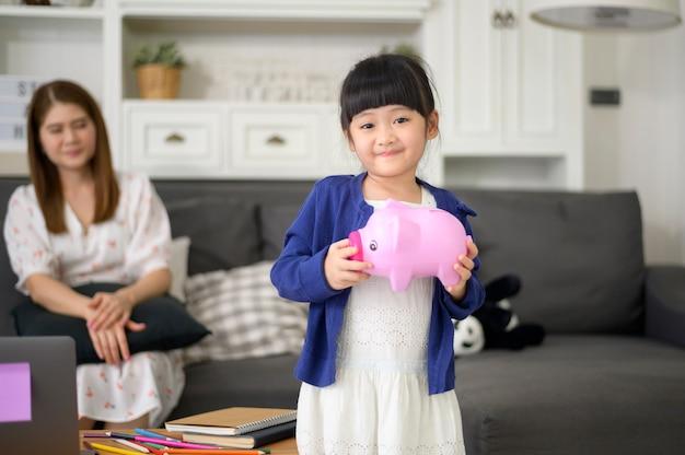 Een aziatische familie onderwijst dochter over spaargeld met een spaarvarken, financieel planningsconcept