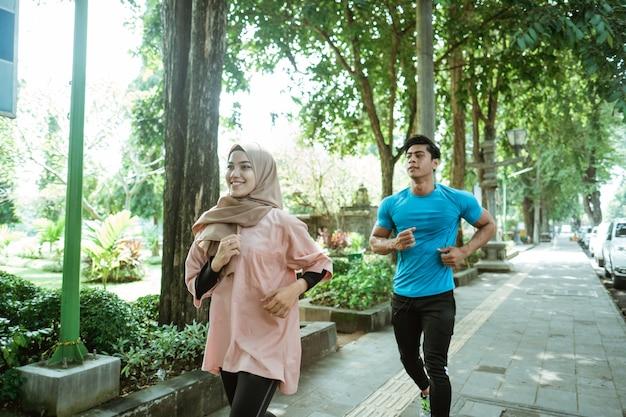 Een aziatische jonge man en een meisje in een sluier die samen joggen tijdens het sporten in de buitenlucht