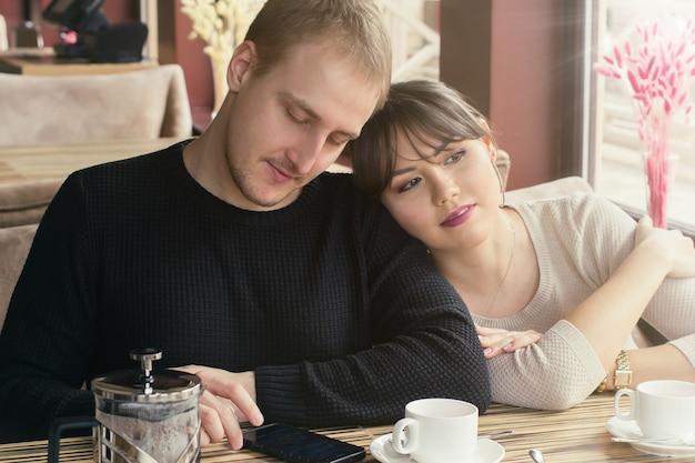 Een aziatische jonge vrouw en een blanke man paar zitten in café. haar hoofd ligt op zijn schouder