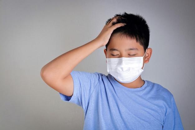 Een aziatische jongen draagt een masker dat zijn mond en neus bedekt en coronavirus of covid-19 voorkomt. gezondheid van kinderen concept