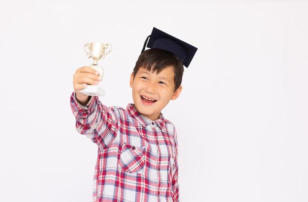 Een aziatische jongen enthousiast over zijn winnende sportmedaille en trofee Premium Foto