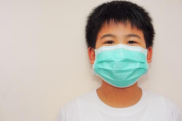 Een aziatische jongen in een wit t-shirt, recht in de camera kijken, met medisch masker op het gezicht en blije ogen. gezondheid, behandeling, bescherming, weerstand en strijd concept.