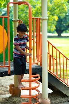 Een aziatische jongen klimt op een speeltoestel in een school.