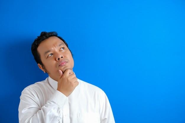 Een aziatische kantoormedewerker die blij is om een briljant idee te vinden, een man die een uitdrukking van overwinning toont en zijn vinger naar boven wijst