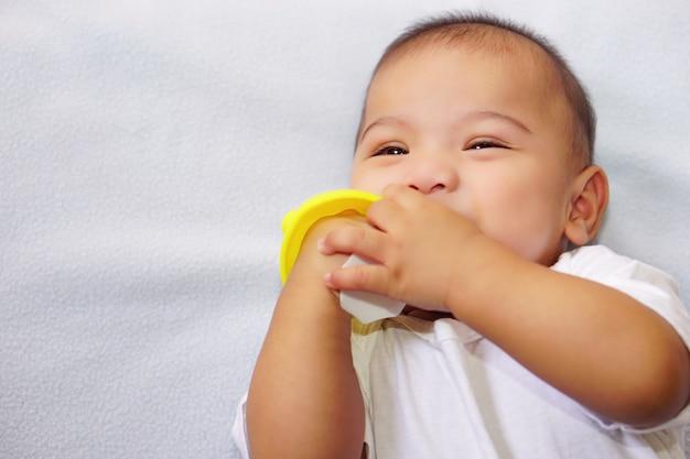Een aziatische kleine schattige baby die bijtspeelgoed bijt op het blauwe stoffen bed voor plezier en geluk