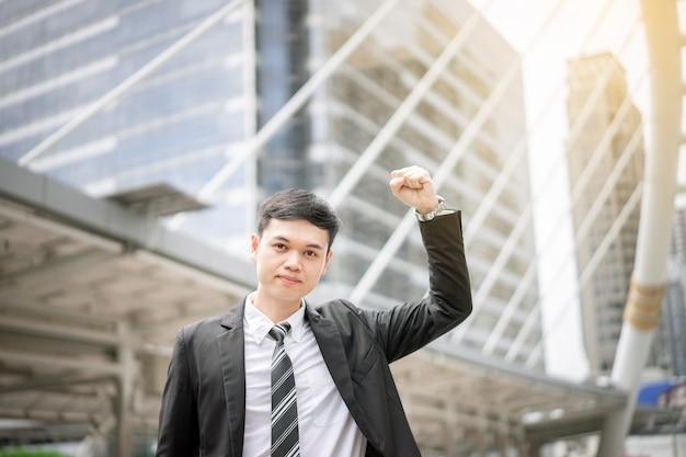 Een aziatische knappe zakenman is erg blij voor zijn succes. hij is een manager die de toenemende winst maakt voor het bedrijf