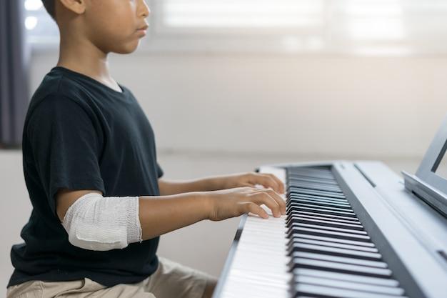 Een aziatische knul aan de gewonde handen bespeelt de piano