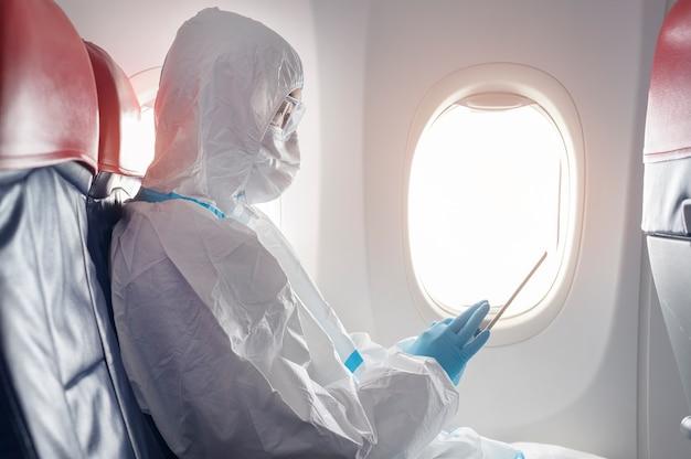 Een aziatische man draagt beschermend pak, ppe-pak in vliegtuig, veiligheidsreisconcept.