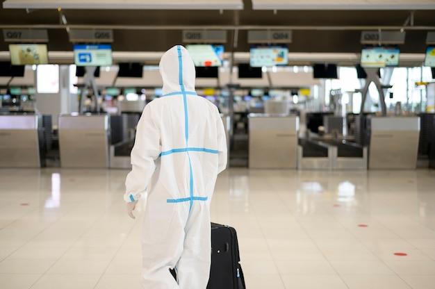 Een aziatische man draagt een pbm-pak op de internationale luchthaven, veiligheidsreizen, covid-19-bescherming, sociaal afstandsconcept.