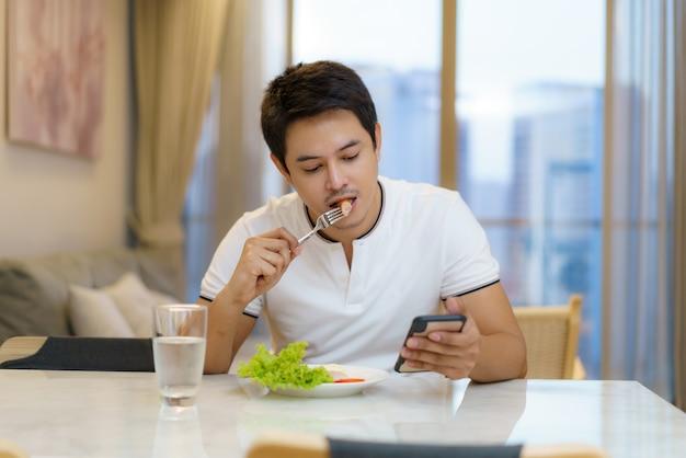 Een aziatische man eet een amerikaans ontbijt terwijl hij achter een stoel zit om te bellen, e-mails of nieuws te lezen in de huiskamer.