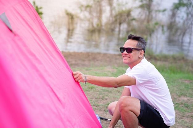 Een aziatische man in witte t-shirt roze tent instellen op camping