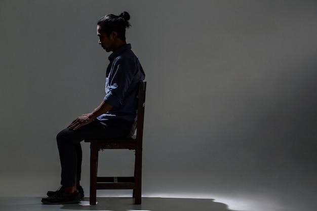 Een aziatische man lijdt aan depressies in de duisternis.