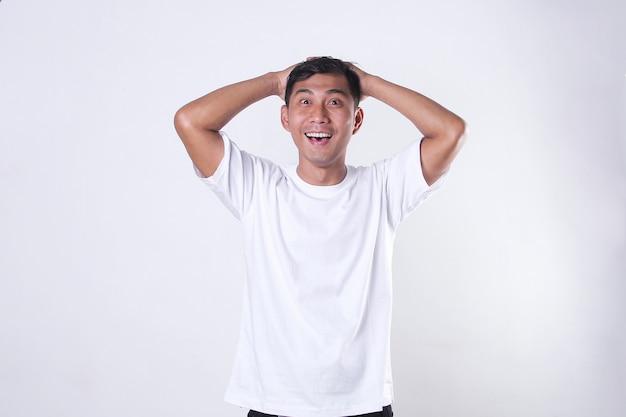 Een aziatische man met een wit t-shirt plaatst zijn handpalmen boven zijn hoofd met zijn ogen en mond open