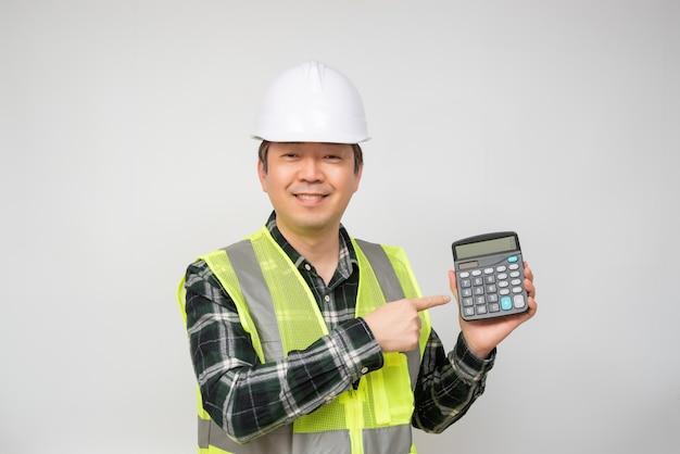 Een aziatische man op middelbare leeftijd die een witte het werk glb en een werkpak draagt dat een calculator in zijn hand houdt.
