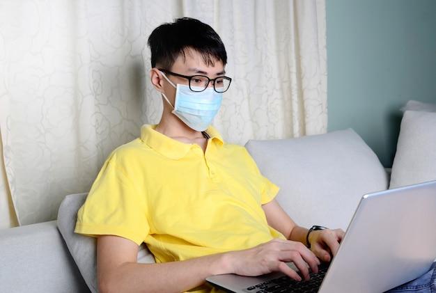 Een aziatische man werkt vanuit huis tijdens pandemisch coronavirus covid-19. ccoronavirus covid 19 geïnfecteerde patiënt in quarantainekamer met behulp van computer.