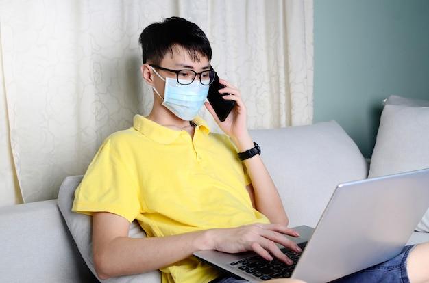 Een aziatische man werkt vanuit huis tijdens pandemisch coronavirus covid-19. ccoronavirus covid 19 geïnfecteerde patiënt in quarantainekamer met behulp van smartphone en computer.