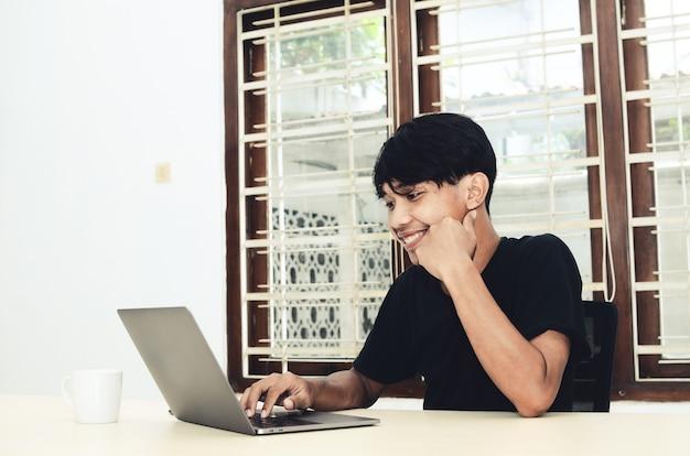 Een aziatische man zit achter een laptop en werkt aan een opdracht