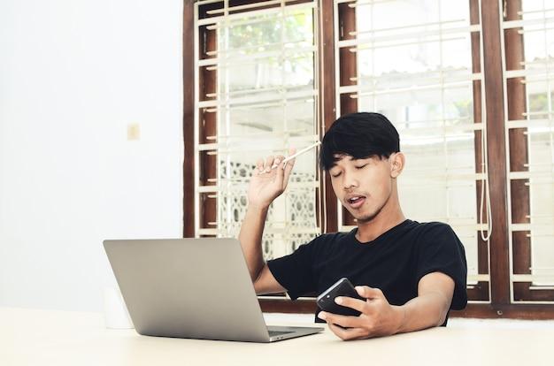 Een aziatische man zit voor de laptop met een bedachtzame uitdrukking