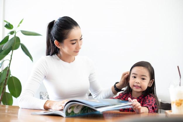 Een aziatische moeder leert haar dochter om een boek te lezen tijdens de pauze van het semester op de levende tafel en met koude melk op tafel thuis. educatieve concepten en activiteiten van het gezin