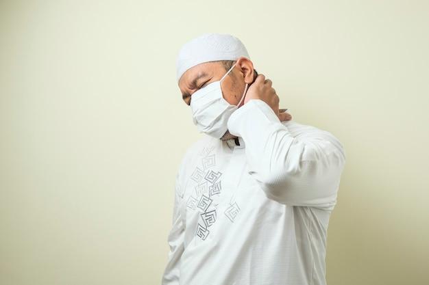 Een aziatische moslim dikke man met een masker die pijn in zijn nek voelt, gebaar houdt zijn nek vast