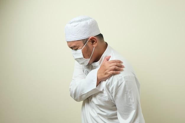 Een aziatische moslim dikke man met een masker die pijn in zijn schouder voelt, gebaar met linkerschouder