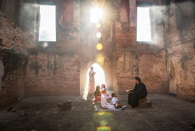 Een aziatische moslimman leerde zijn zoon en jonge dochter om gebeden tot god te lezen in een moskee met zonlicht dat door ramen en deuren scheen.