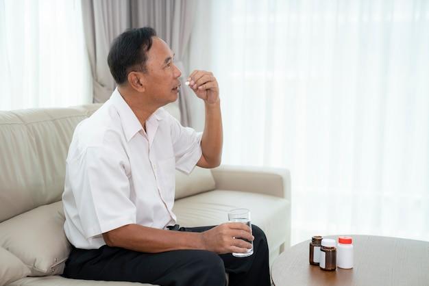 Een aziatische oude man gaat pillen slikken