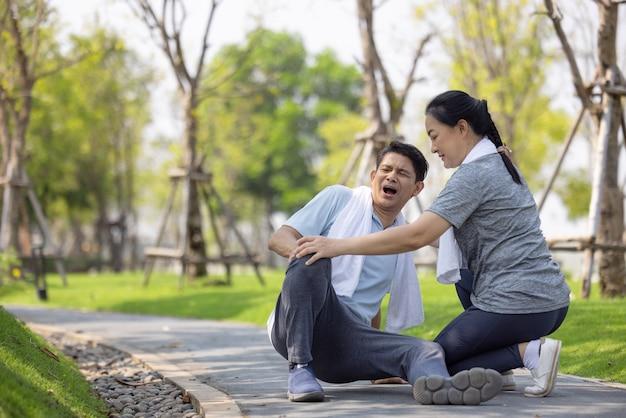 Een aziatische oudere of senior man die tijdens het hardlopen op de vloer in het park valt, heeft pijn in de knie.