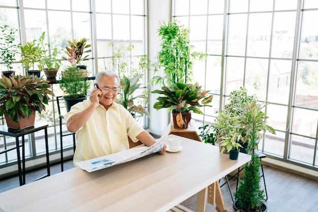 Een aziatische senior gepensioneerde man in vrijetijdskleding met een mobiele telefoon met een glimlach tijdens het lezen van een krant.