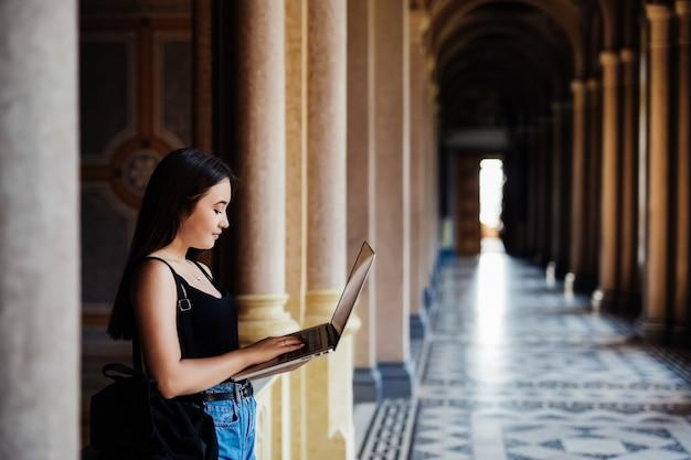 Een aziatische student die aan haar laptop op campus werkt