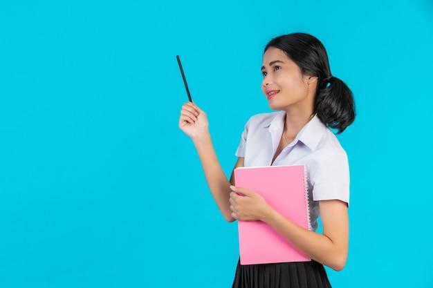 Een aziatische studente met een met haar roze notitieboekje op een blauw.
