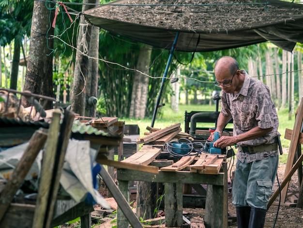 Een aziatische timmerman die hout met elektrische planer vormt
