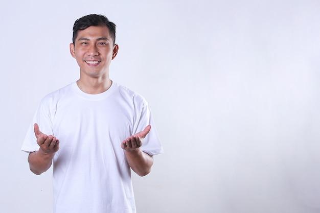 Een aziatische volwassen man die een wit t-shirt draagt en zijn armen opent met kopieerruimte